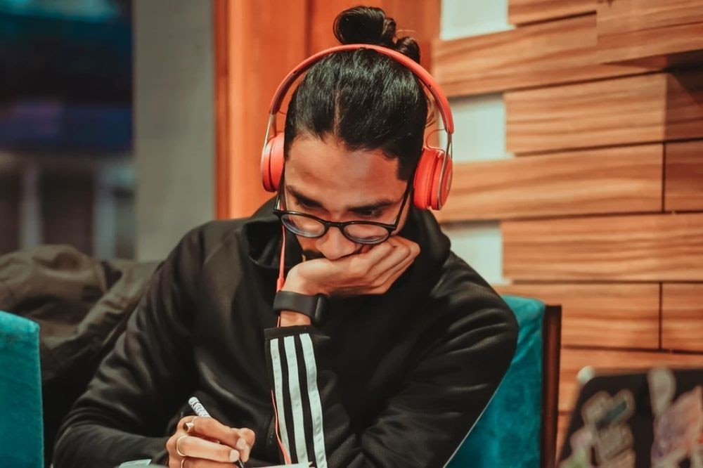 young man with red headphones writing - Wavve.co